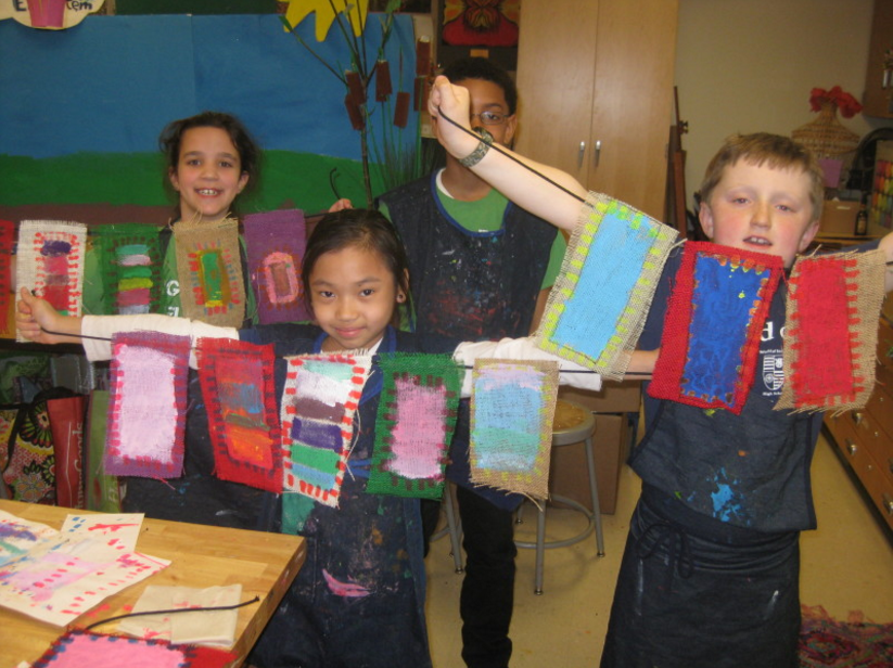 Group of students holding up their art projects