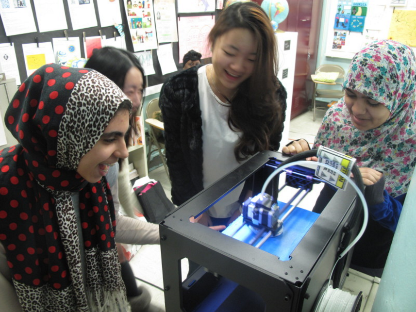 Students with their teacher, gathered around a 3D printer